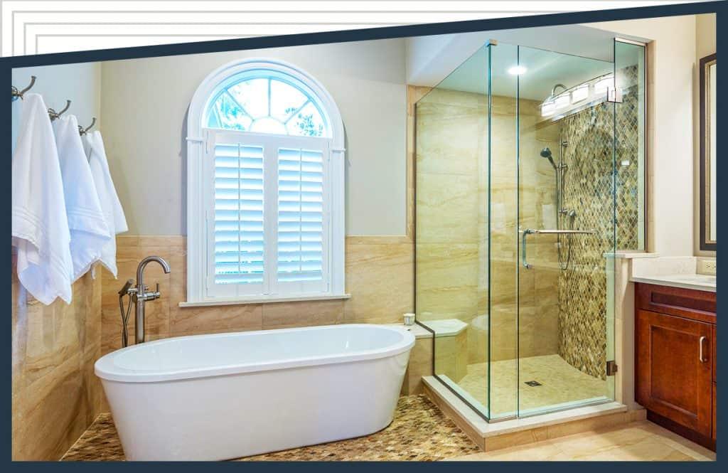 窗户下的浴缸附近挂着毛巾。在水槽和梳妆台旁边,有一个带有彼得森淋浴门的Aldora玻璃浴室。