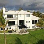 大型白色住宅的无人机视图,黑色装饰,正面视图,住宅区,多个双面板冲击窗,由Aldora设计的FS-300 Maxi view冲击店面窗,修剪整齐的草坪,棕榈树,热带环境