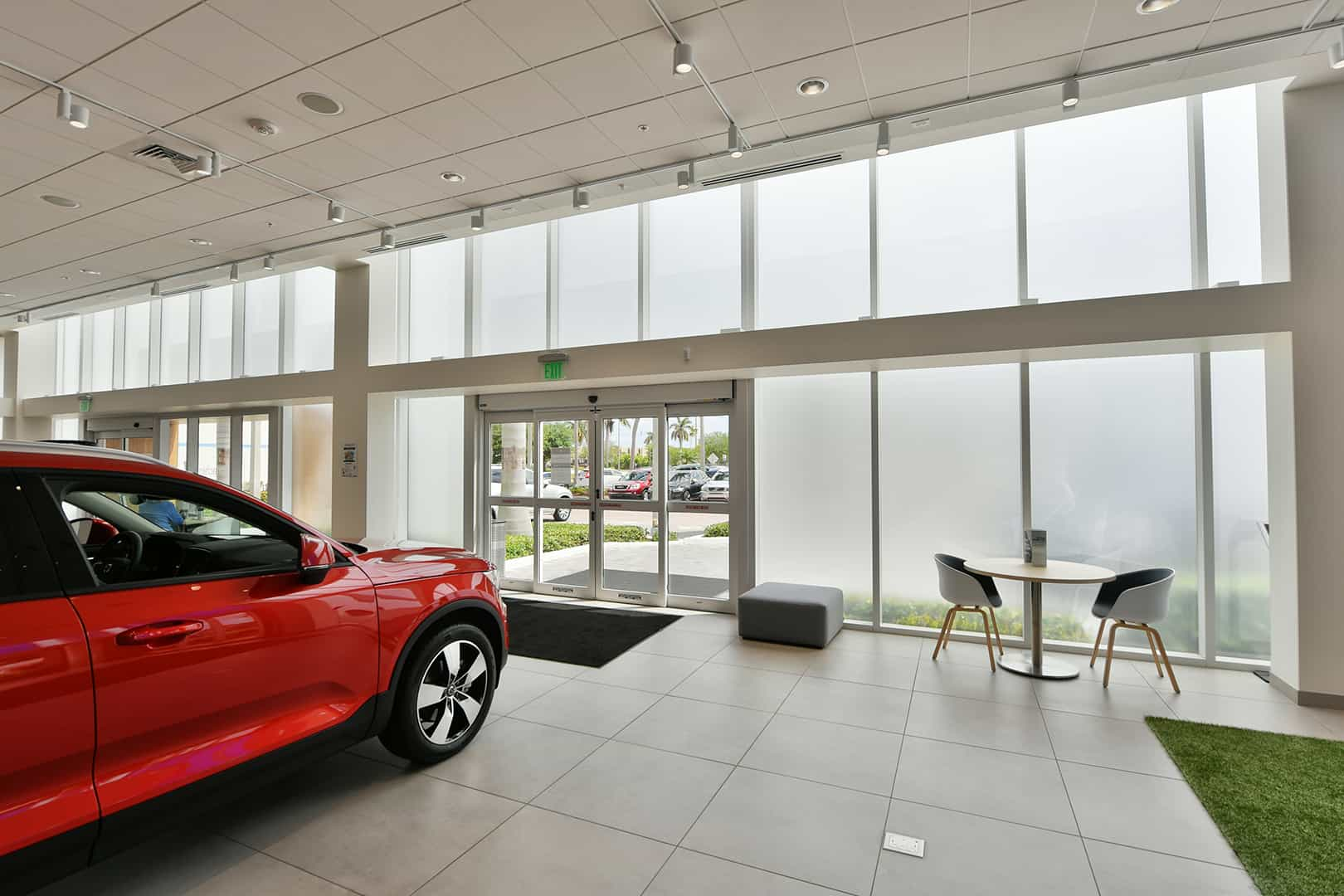 Interior view of car dealership looking through frosted FS-300 Maximum View Impact Storefront windows by Aldora, two sets of sliding glass doors, white tile floor and ceiling, seating area, red showcase vehicle in room