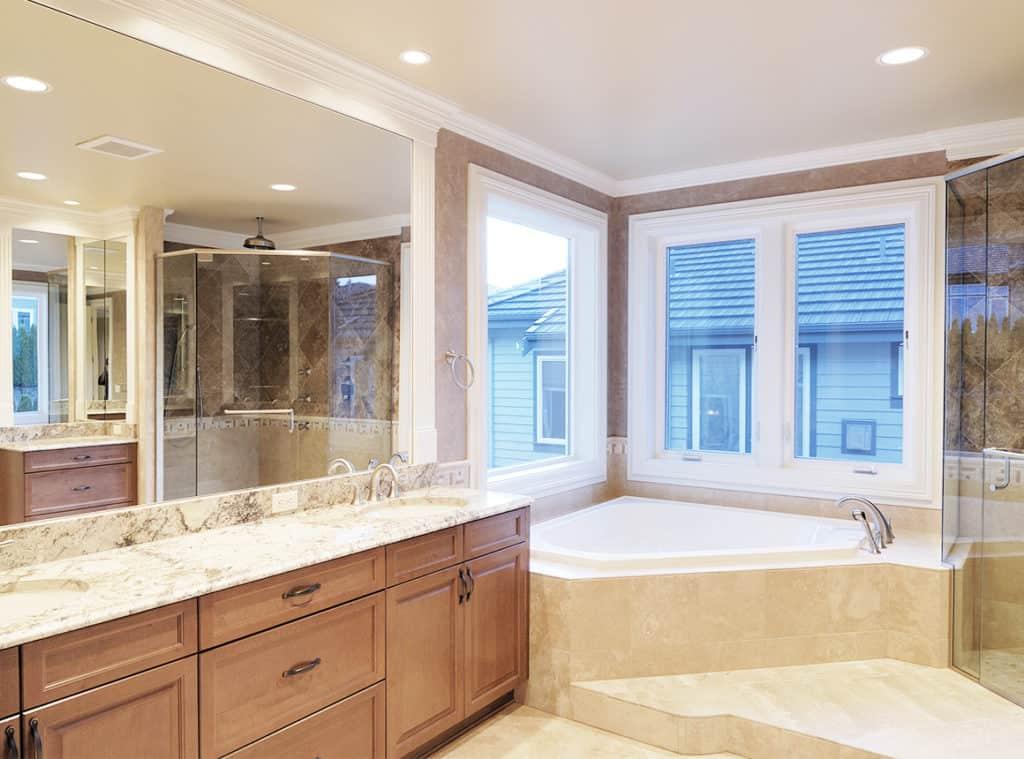 浴缸在浴室的角落里,窗户下面。一个阿尔多拉镜子,水槽和一个梳妆台盖在左边的墙上。从镜子的反射中可以看到步入式玻璃淋浴。
