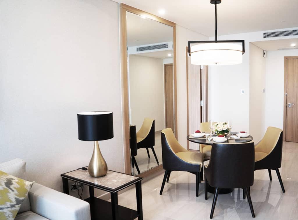 在门厅和门的前面,有一张带有四把椅子的固定餐桌,在一盏吊灯下。桌子左边的墙上挂着一面从地板到天花板的Aldora镜子。沙发旁边有一张带灯的边桌。