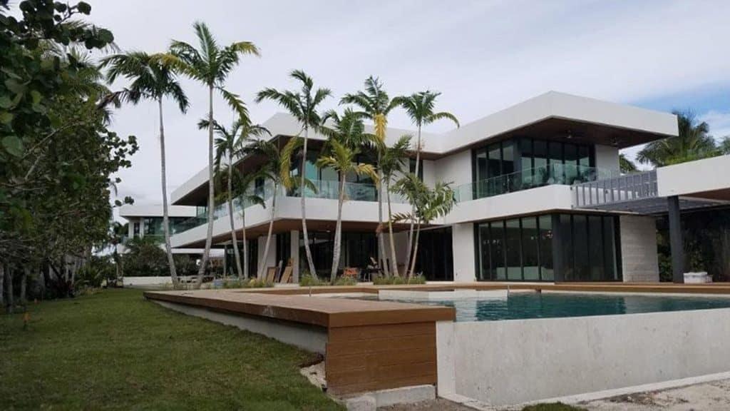 两层白色住宅,玻璃冲击墙,一楼和二楼的落地窗与黑色装饰,来自Aldora的SMI-175影响店面系统,灰色的突出柱子,前景的无限游泳池与木装饰,棕榈树,热带景观