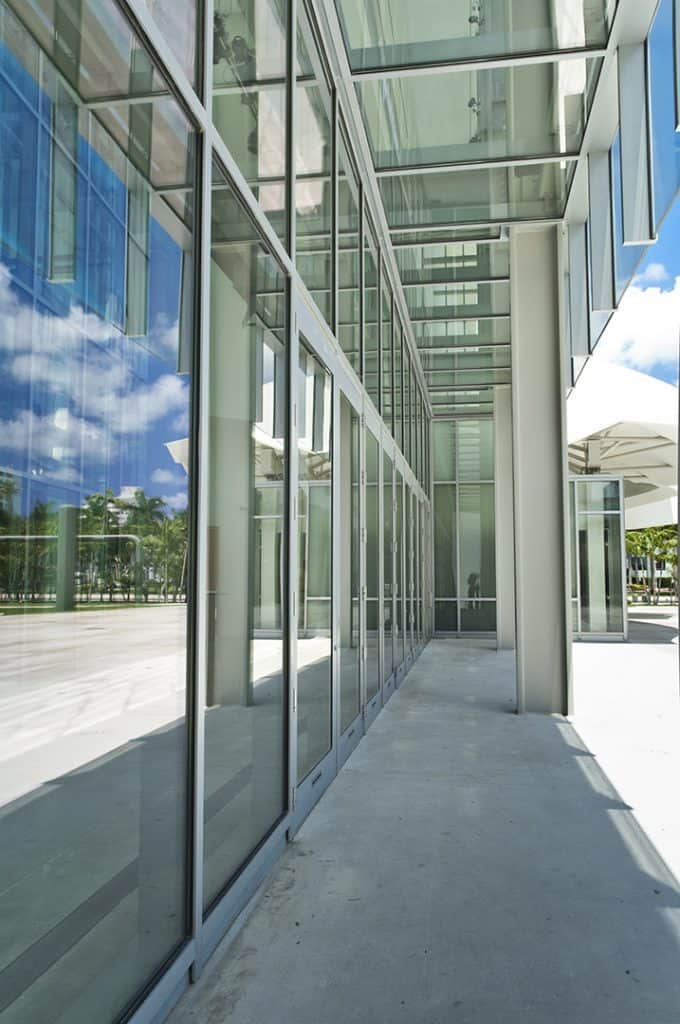 Side angle view of K2-Summit Impact Doors by Aldora, doors are surrounded by glass impact curtain walls, sidewalk leading to doors