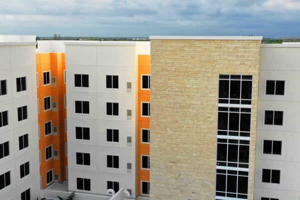 多级橙色建筑,带灰色外输出和石头复印,FS-300冲击前置双面板窗户与铝制框架,栅栏窗帘墙窗户在建筑物的螺纹薄膜部分