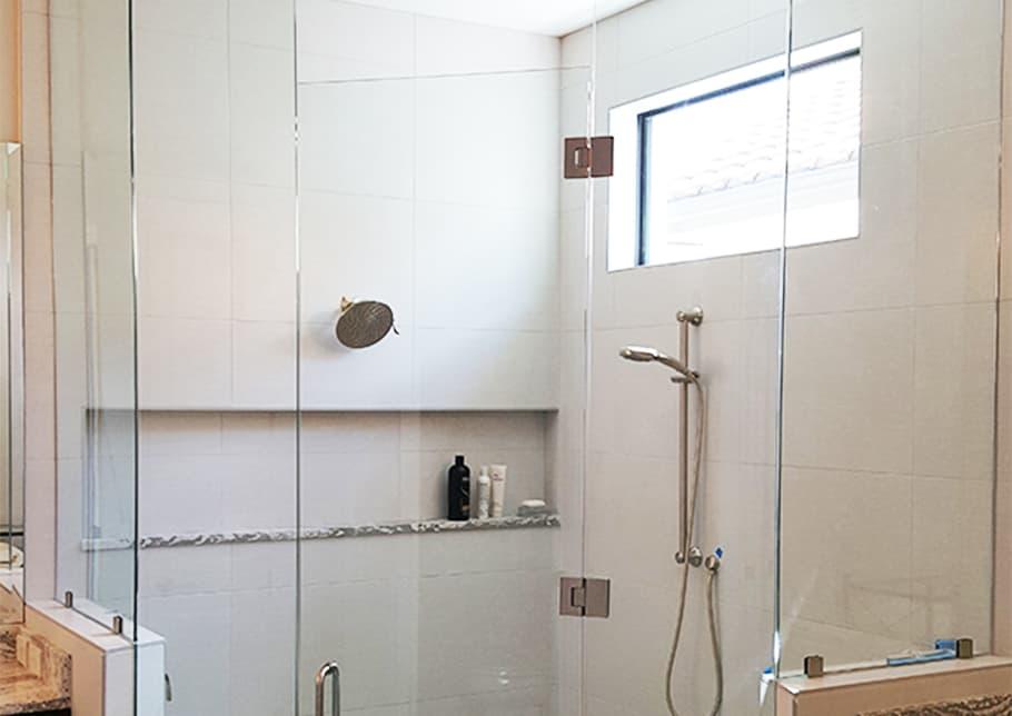 淋浴间采用Aldora定制玻璃,包括门。瓷砖墙壁上有水龙头、淋浴喷头、架子和窗户