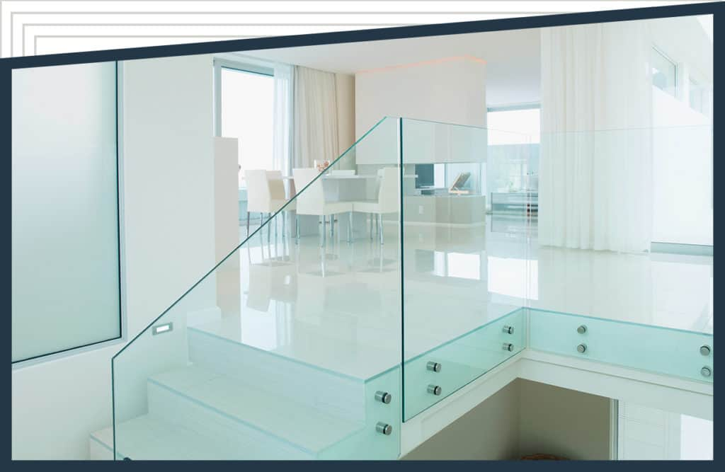 Aldora tempered glass acts as a railing on a staircase leading to a sitting room. White curtains line the windows, white chairs sit around a dining table and a white fireplace is beyond the table.