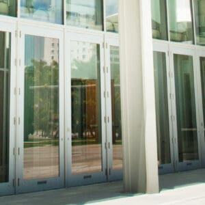 Angled view of commercial glass doors by Aldora, curtain wall windows above and surrounding doors to create building walls, side walk in front of building