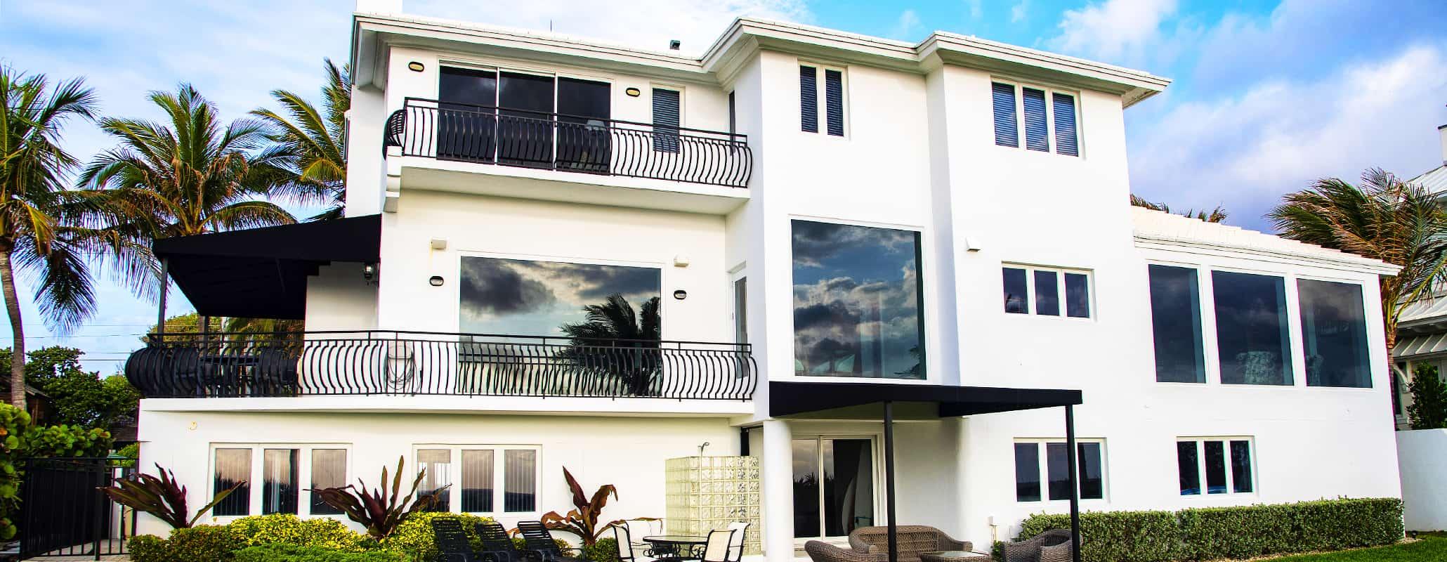 俯瞰昂贵住宅的地面景观,由Aldora设计的前置系统玻璃窗,冲击玻璃,带有阳台的滑动玻璃门,修剪整齐的草坪,棕榈树