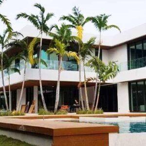 两层白色住宅,玻璃冲击墙,地板到天花板绝缘的Aldora窗户在第一和第二层与黑色装饰,SMI-175影响店面系统从Aldora,灰色的强调柱子,前景无限游泳池与木装饰,棕榈树,热带景观