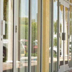 窗户和Aldora无冲击玻璃门排列在橙色建筑的墙壁上。砖铺的天井和覆盖在门前。
